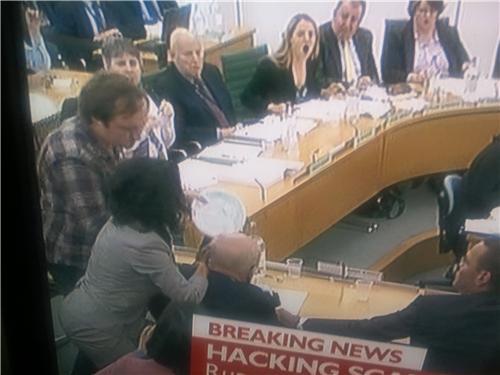 A pie-thrower targets Rupert Murdoch during MP hearings