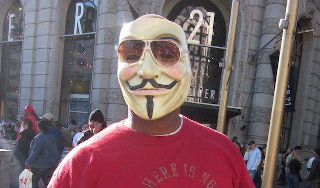 A protestor in San Francisco wears the Guy Fawkes mask that is the signature of Anonymous.
