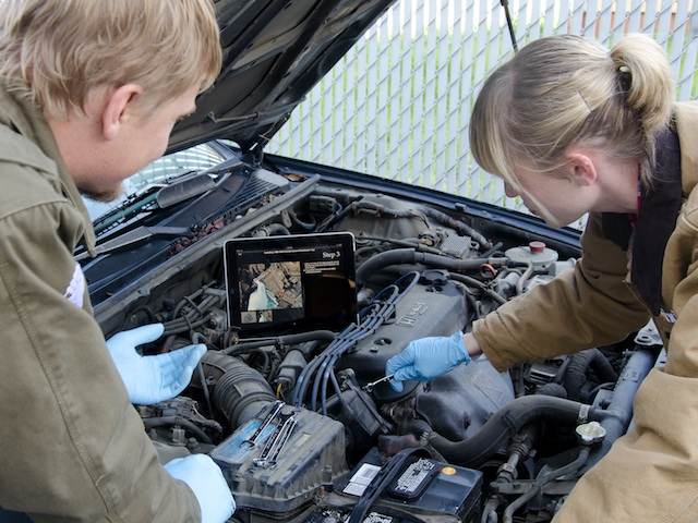 Photo of two people repairing a car engine with an iPad as a repair manual.