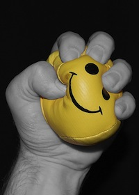 Hand squeezing a yellow stress ball