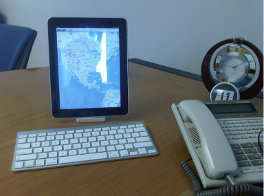 iPad and wireless keyboard on an office desk, with an office phone