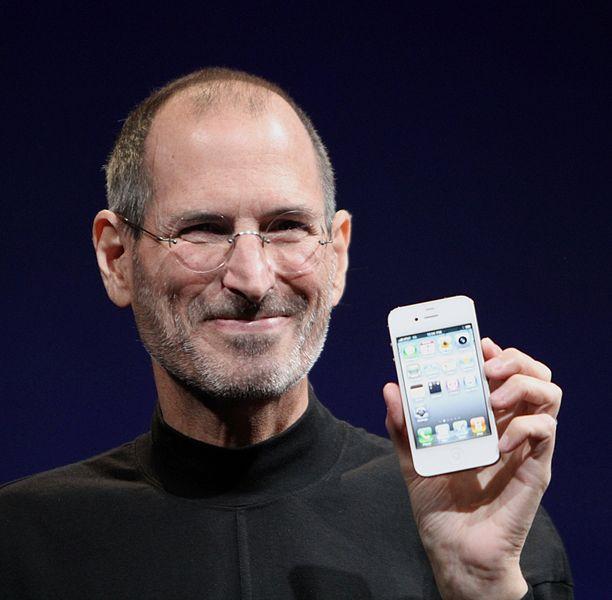 Steve Jobs holding an iPhone.