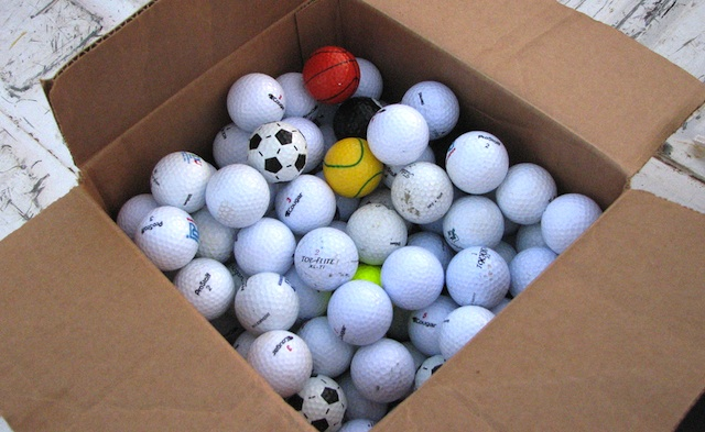 Box of golf balls, mostly white ones