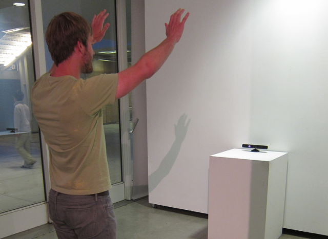 Person interacting with a Kinect in an art gallery