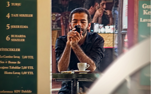 Man in Instanbul cafe using a cellphone