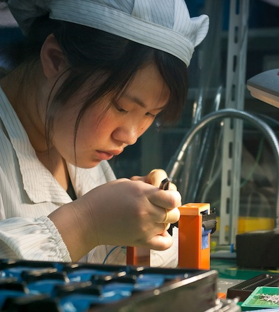 Chinese worker assembles a camera