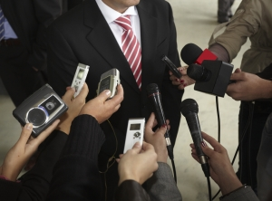 Stock photo of a man in a suit being surrounded by journalists with microphones