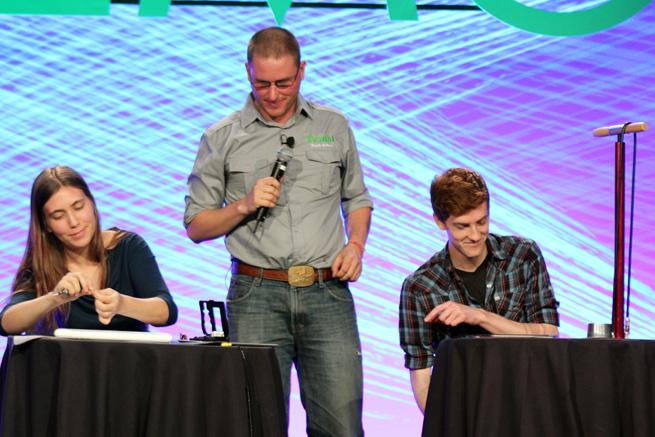 Dozuki founder Kyle Wiens onstage with volunteers using iPad-based manuals