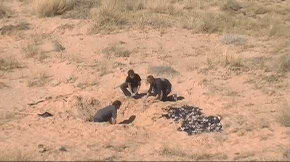Men digging up E.T. games in the desert