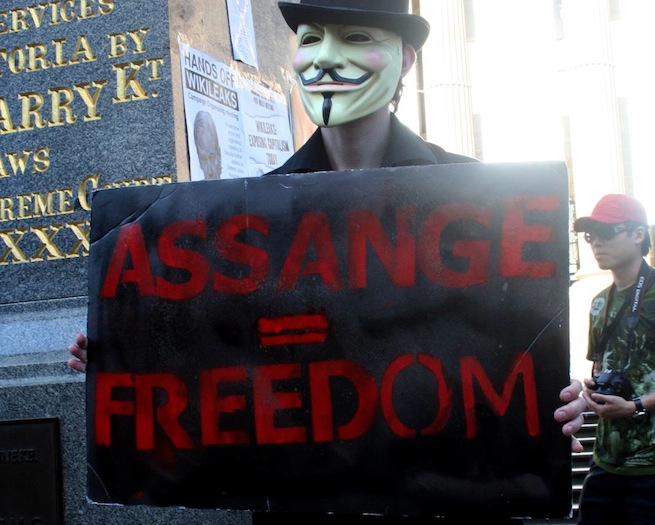 "Anonymous protester holds up ""Assange = Freedom"" sign"