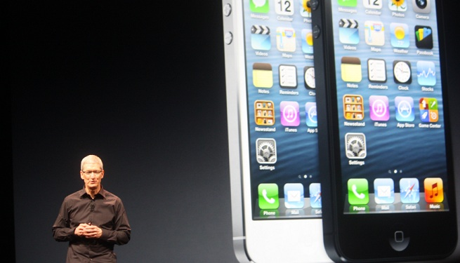 Apple CEO Tim Cook, with two giant iPhone 5 images behind him