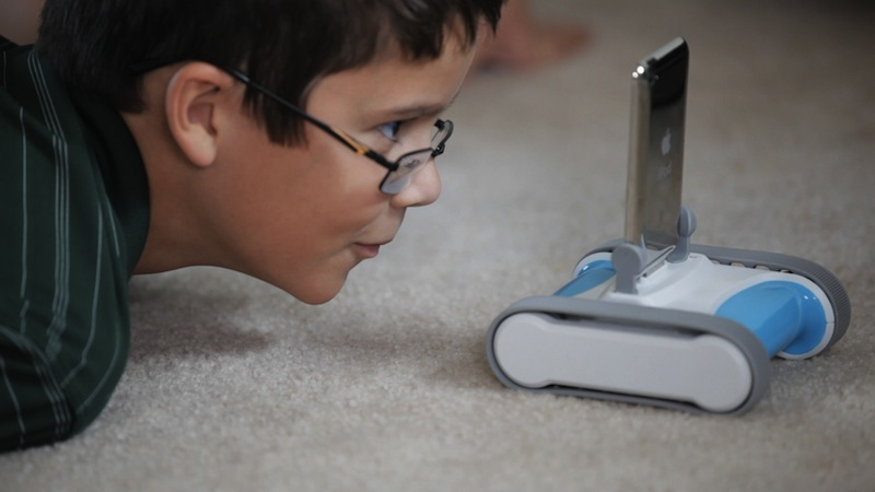 A child stares at a dimunitive Romo, an iOS-powered robot.