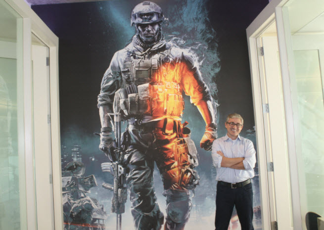 Frank Gibeau  standing in front of promotional art for Battlefield.