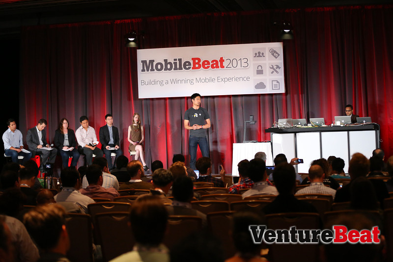 A panel of expert judges oversee a startup pitch at MobileBeat 2013.