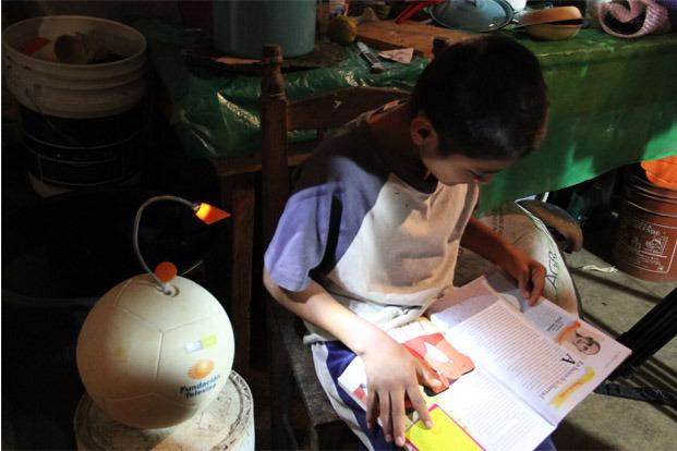 SOCCKET shining light on a student doing his homework.