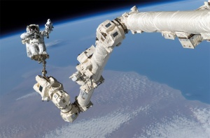 Astronaut Stephen K. Robinson anchored to the end of Canadarm2