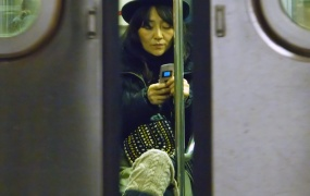 A woman uses her cell phone on a New York City subway train.