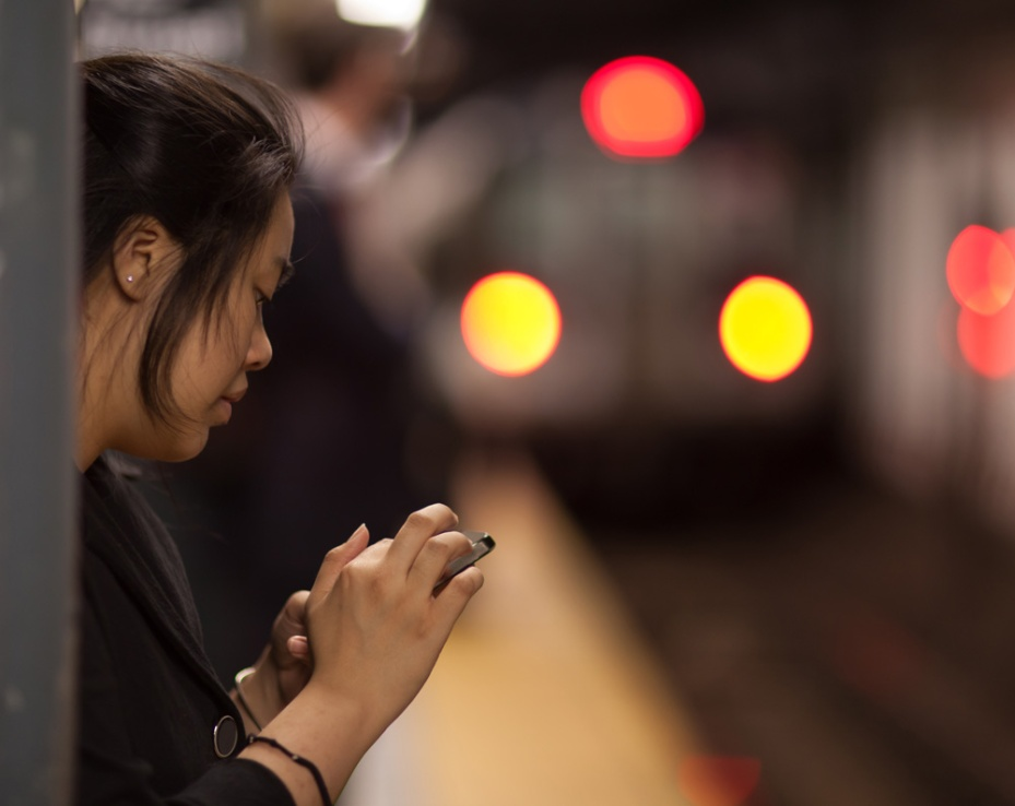 A woman uses her iPhone while waiting in a New York City subway station.