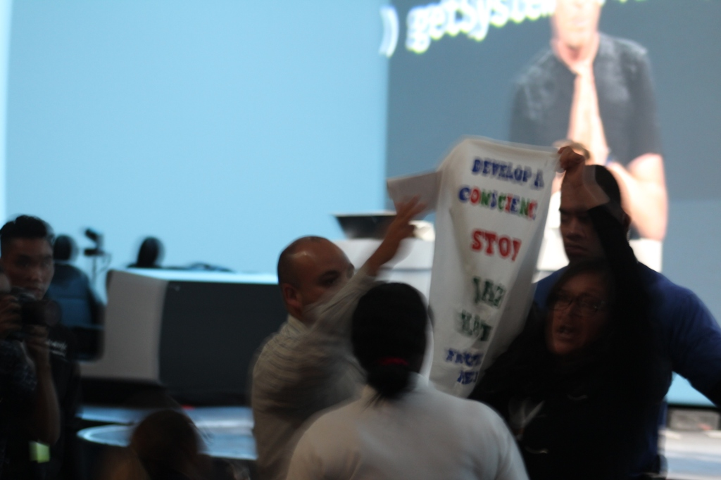 """""""Stop Jack Halprin,"""" the protester's poster says. """"Develop a conscious."""""""