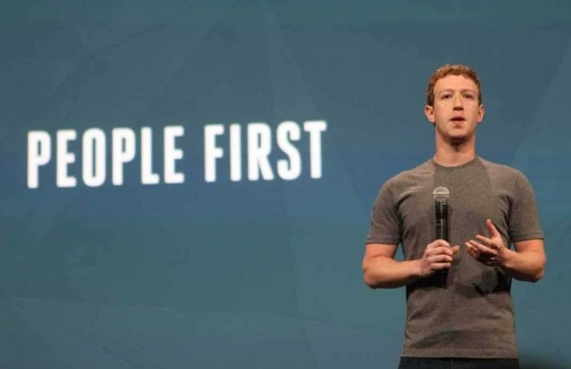 """People first,"" the slide behind Facebook founder Mark Zuckerberg proclaims."