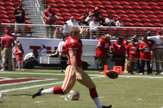 A 49ers kicker warms up on the field.