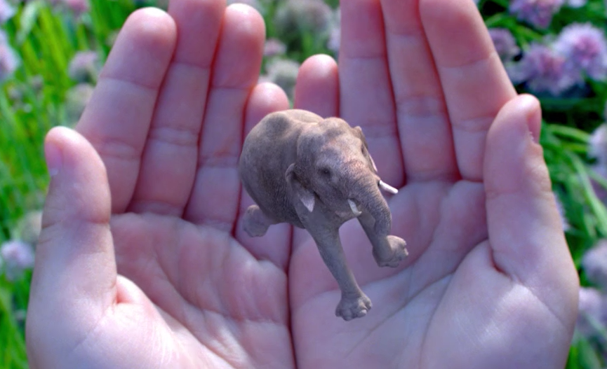 A tiny, photorealistic elephant dances in someone's hands on the Magic Leap website.