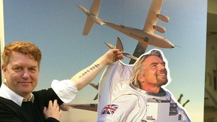 Would-be Virgin Galactic passenger Gisli Gislason shows off his 'DNA of Flight' tattoo in a photograph with a cut-out of Virgin's Richard Branson and SpaceShipTwo