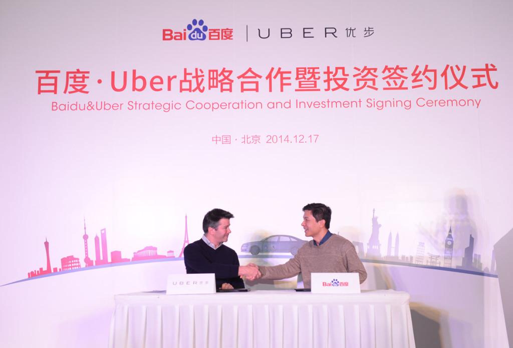 Uber CEO Travis Kalanick (left) shakes hands with Baidu chairman and CEO Robin Li.