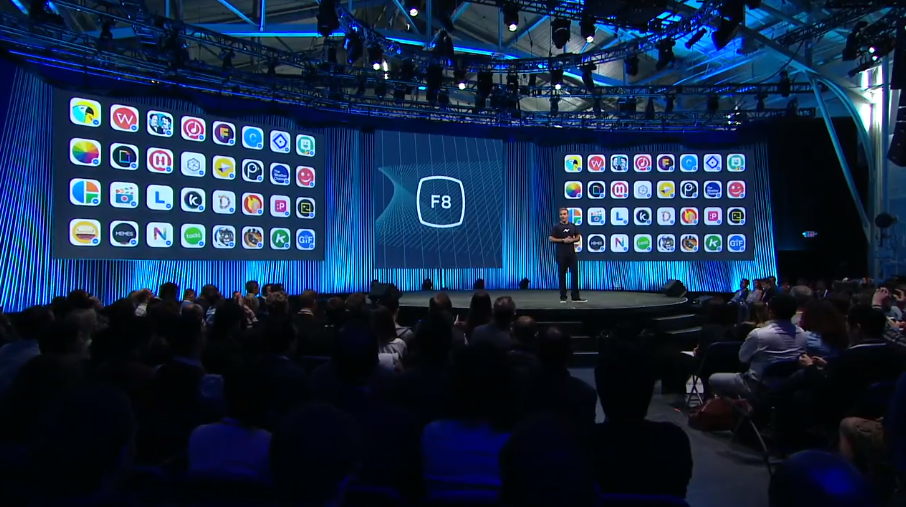 Facebook executive David Marcus onstage at F8, with screens showing the 40 launch partners for the company's new Messenger Platform. (March 25, 2015)
