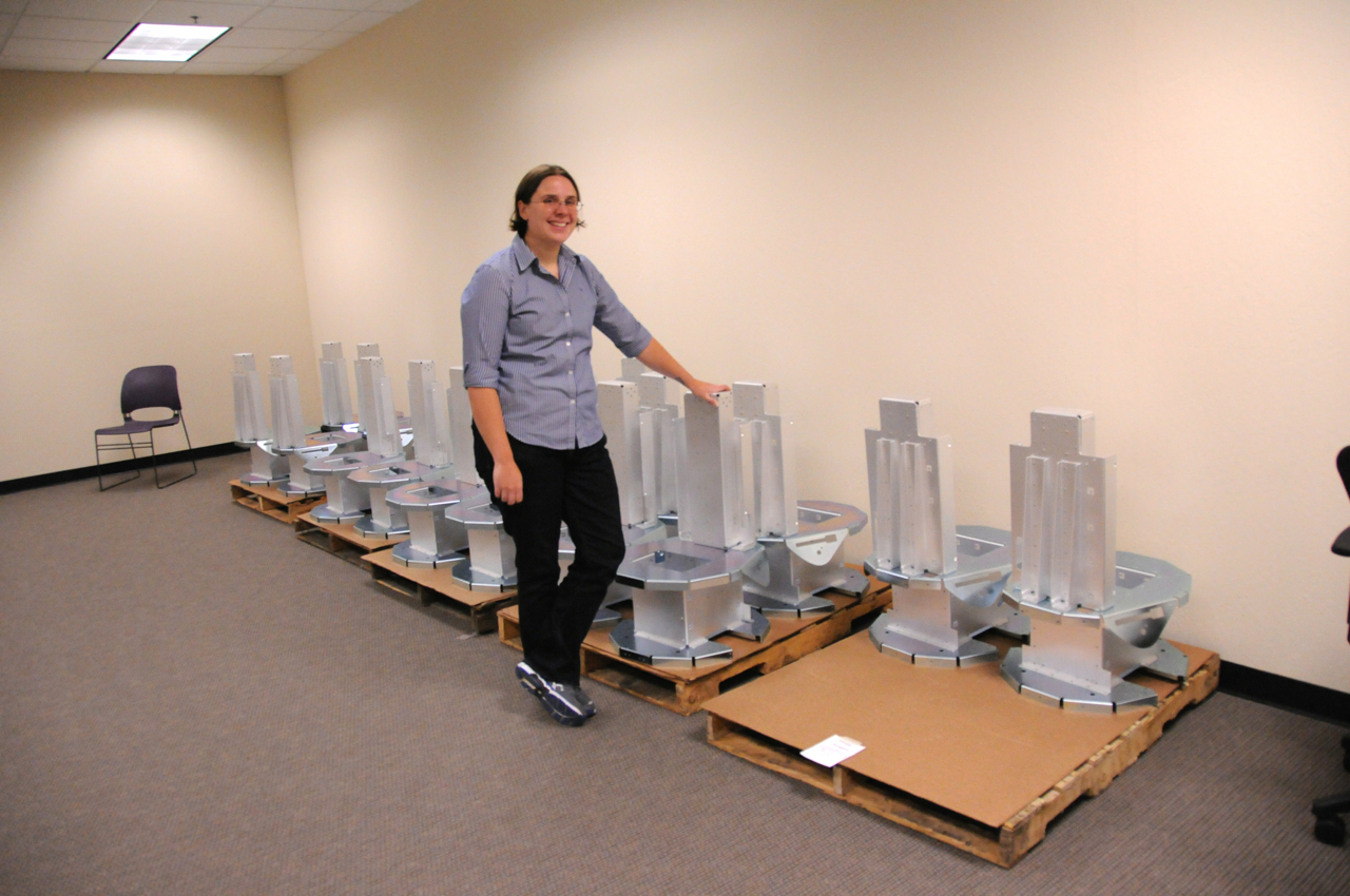Fetch Robotics CEO Melonee Wise, standing in front a a group of sheet-metal robot bases.