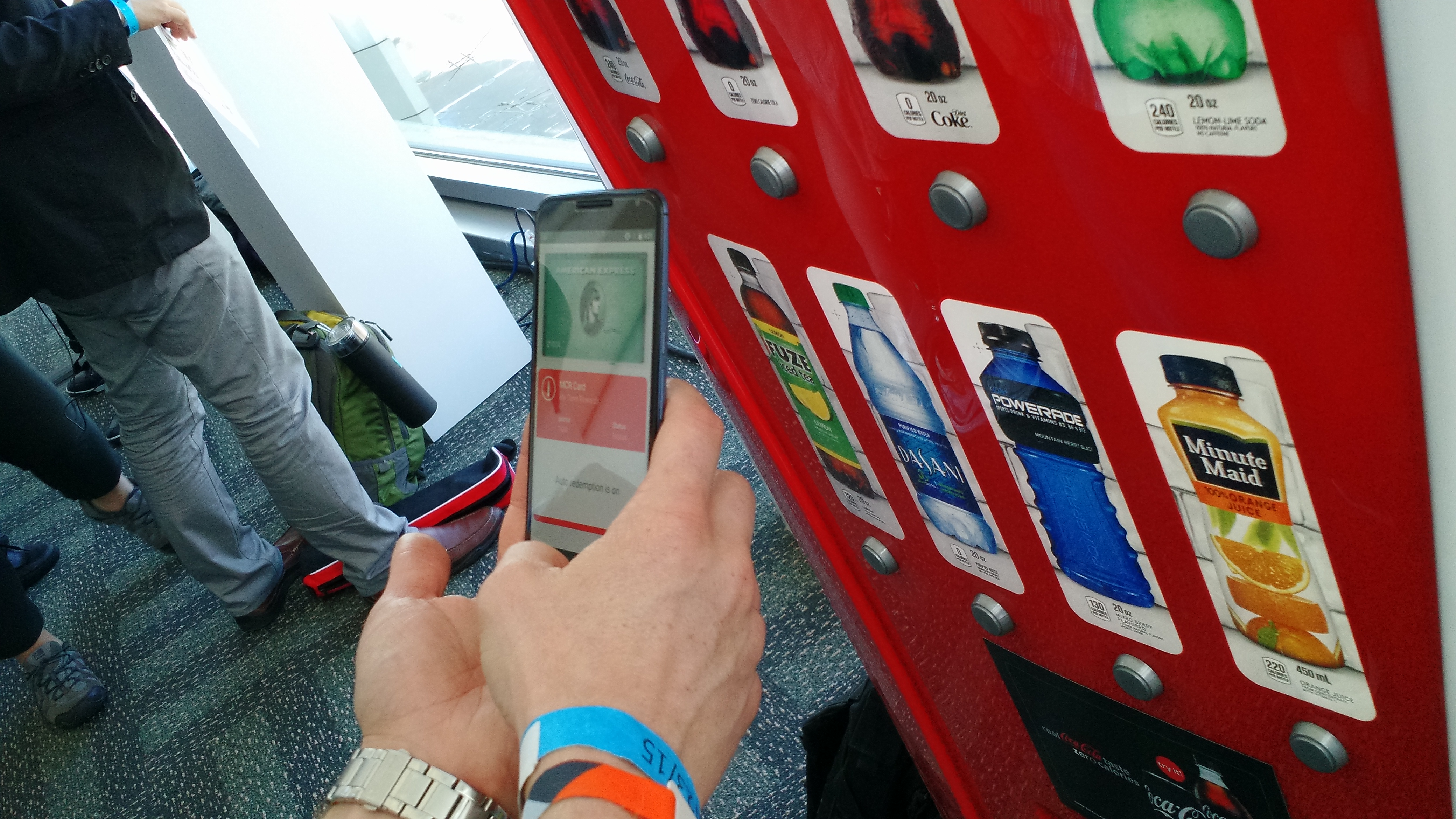 Android Pay being demonstrated on a Coke machine. It's using an American Express card and a Coca-Cola loyalty program.