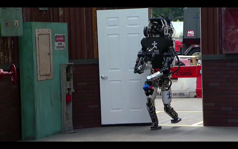 An IHMC Robotics robot opens and goes through a door during the 2015 DARPA Robotics Challenge in Pomona, Calif., on June 5.