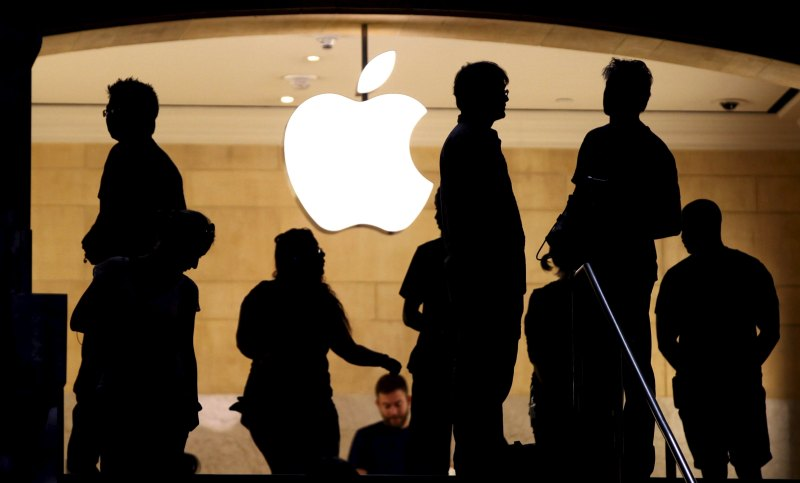 Customers stand beneath an Apple logo at the Apple store in Grand Central station in New York City, July 21, 2015.