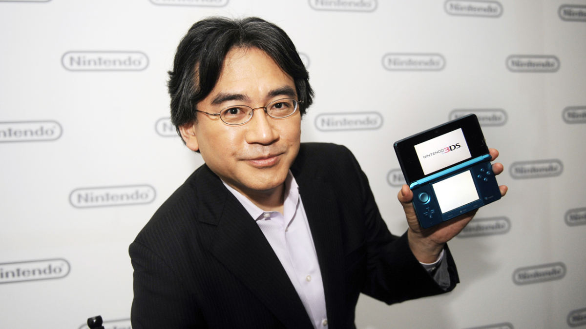 Iwata holding a Nintendo 3DS.
