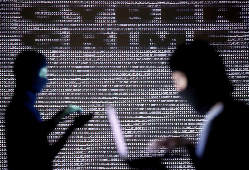 People wearing balaclavas are silhouetted as they pose with a laptops in front of a screen projected with the word 'cyber crime' and binary code, in this picture illustration taken in Zenica October 29, 2014. REUTERS/Dado Ruvic