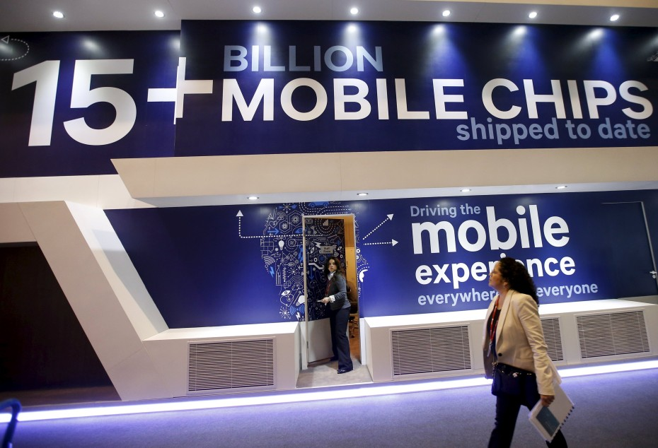 File photo shows a woman walking past an advertisement on the Qualcomm stand at the Mobile World Congress in Barcelona