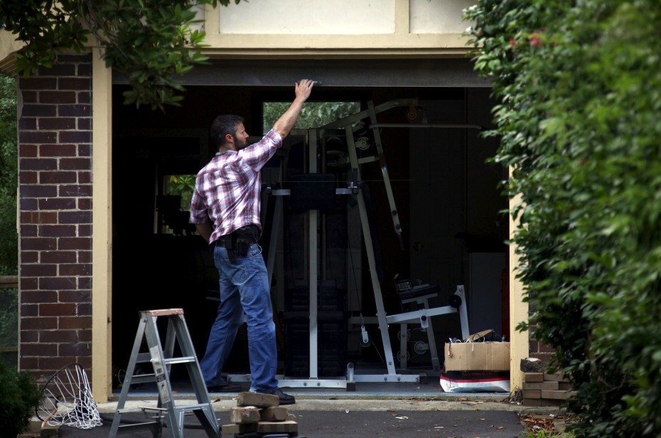 An Australian Federal Police officer closes the door of the garage after searching the home of probable creator of cryptocurrency bitcoin Craig Steven Wright in Sydney's north shore December 9, 2015
