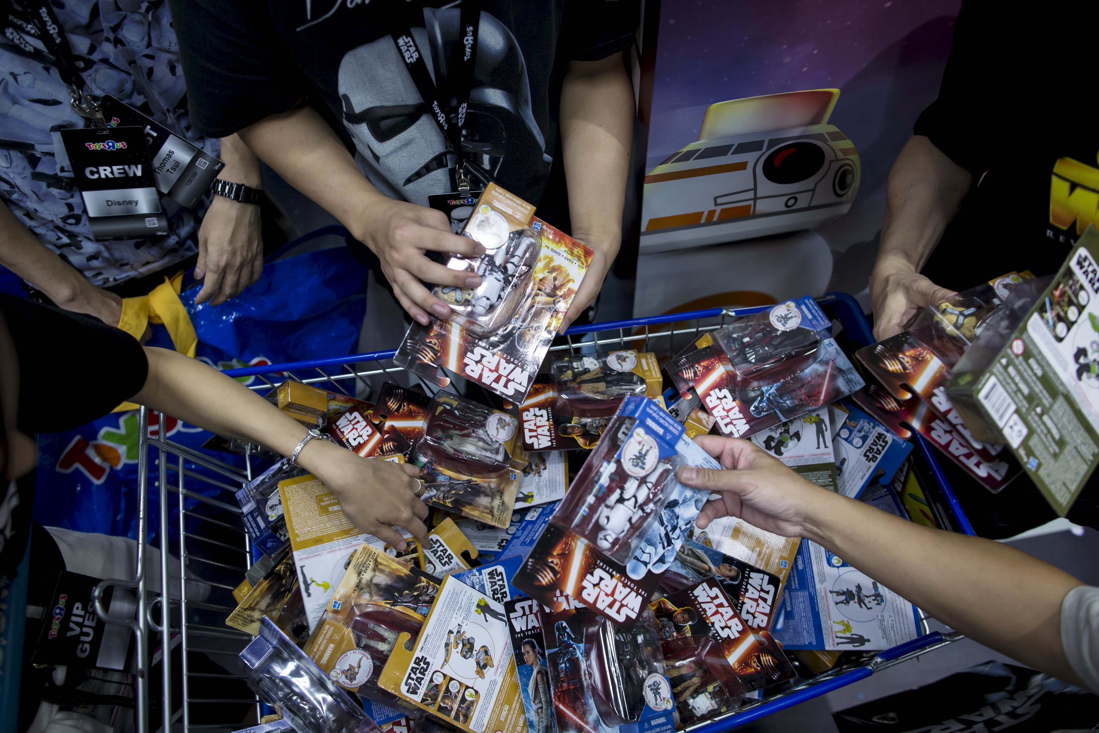 """Customers pick new toys from the upcoming film """"Star Wars: The Force Awakens"""" on """"Force Friday"""" in Hong Kong, China, in this September 4, 2015 file photo. REUTERS/Tyrone Siu/Files"""