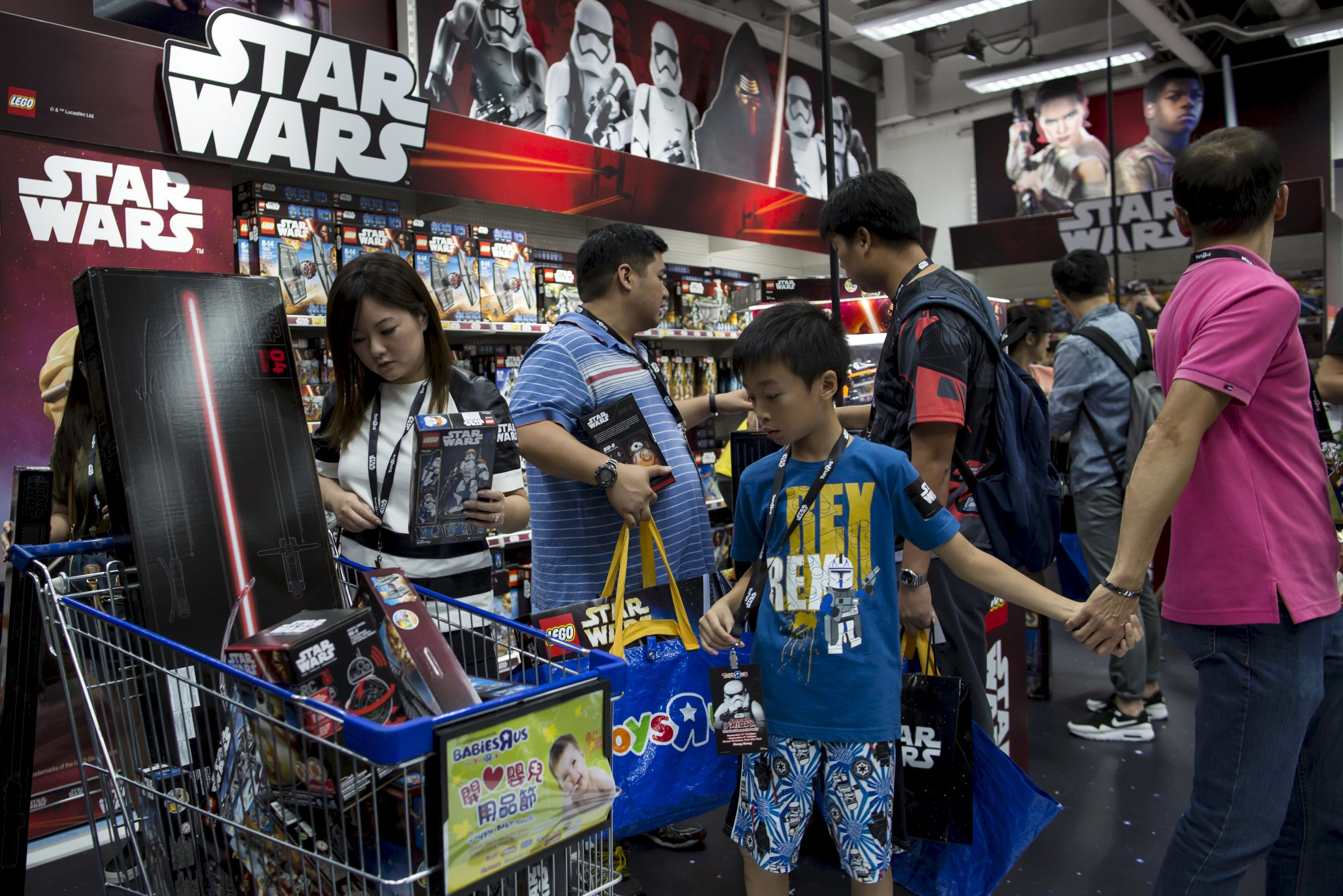 "Customers pick new toys from the upcoming film ""Star Wars: The Force Awakens"" on ""Force Friday"" in Hong Kong, China, in this September 4, 2015 file photo. REUTERS/Tyrone Siu/Files"