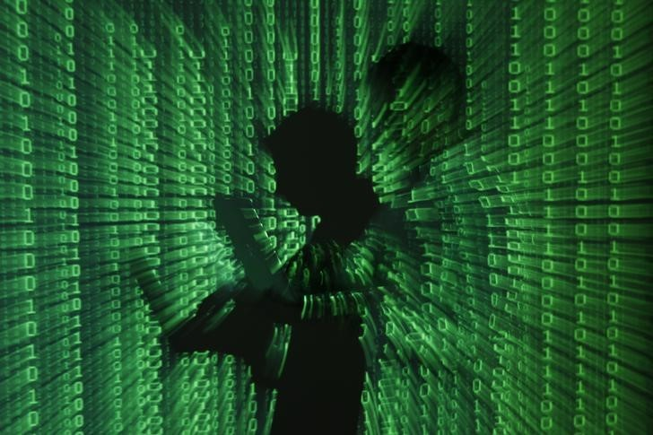 An illustration picture shows a projection of binary code on a man holding a laptop computer, in an office in Warsaw June 24, 2013.