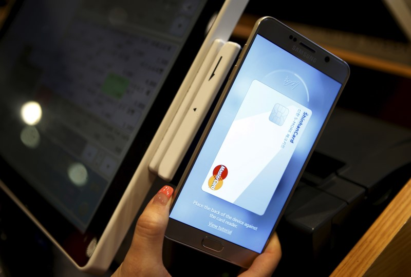 An employee demonstrates a Samsung Pay, Samsung's new mobile payment system at a shop in Seoul, South Korea, September 4, 2015. The system allows customers to pay for goods by simply placing their handsets on or next to a point-of-sale terminal.