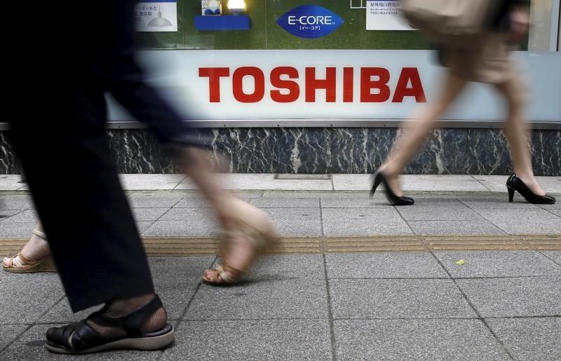 Pedestrians walk past a logo of Toshiba Corp outside an electronics retailer in Tokyo September 14, 2015.