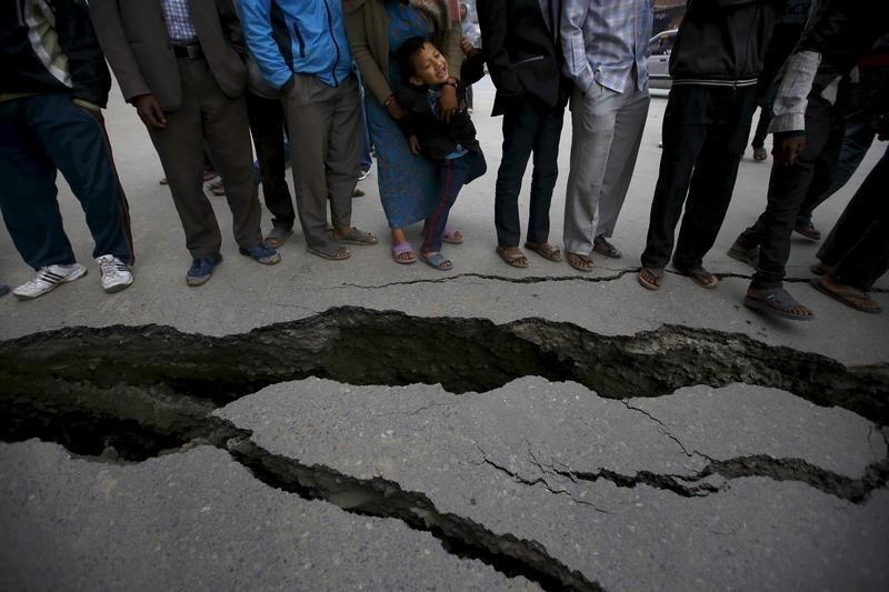 People gather near the cracks on the road caused by an earthquake in Bhaktapur, Nepal April 26, 2015. Rescuers dug with their bare hands and bodies piled up in Nepal on Sunday after an earthquake devastated the heavily crowded Kathmandu valley, killing at least 1,900, and triggered a deadly avalanche on Mount Everest.