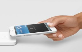 Apple Pay is shown in use with Square's contactless card reader, which also supports Google Pay.