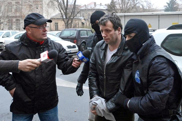 Marcel Lazar Lehel, 40, is escorted by masked policemen in Bucharest, after being arrested in Arad, 550 km (337 miles) west of Bucharest January 22, 2014.