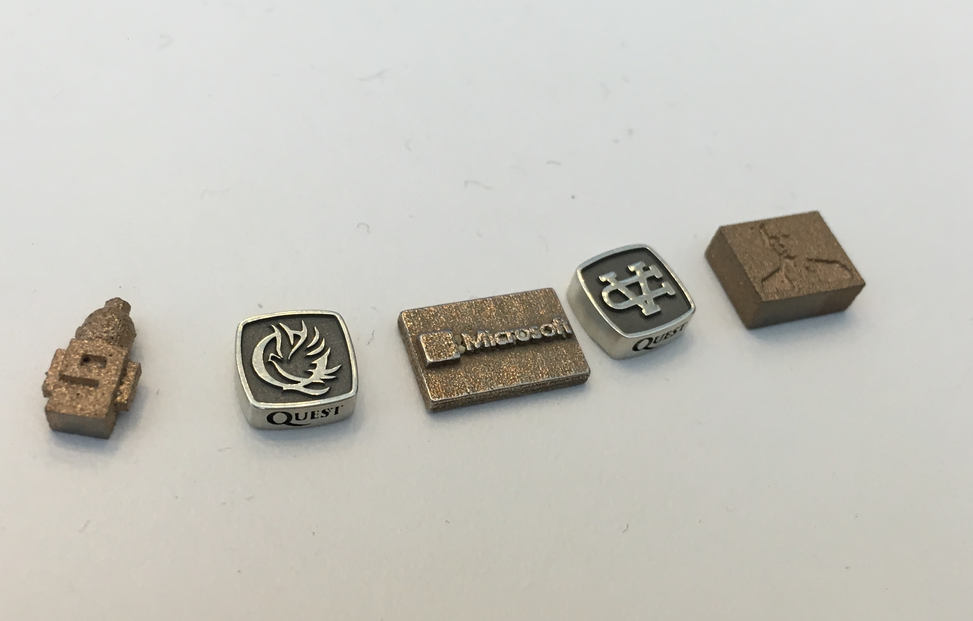 Some of the pieces that will be tested in space. The one on the far left represents Microsoft's Channel 9. The middle one is Microsoft's logo. The one of the far right is a bust of Microsoft chief executive Satya Nadella. The second and fourth are logos of the Valley Christian Schools.