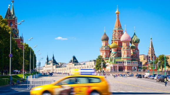 Red Square with the Kremlin and St. Basil Cathedral with yellow taxi car in foreground.