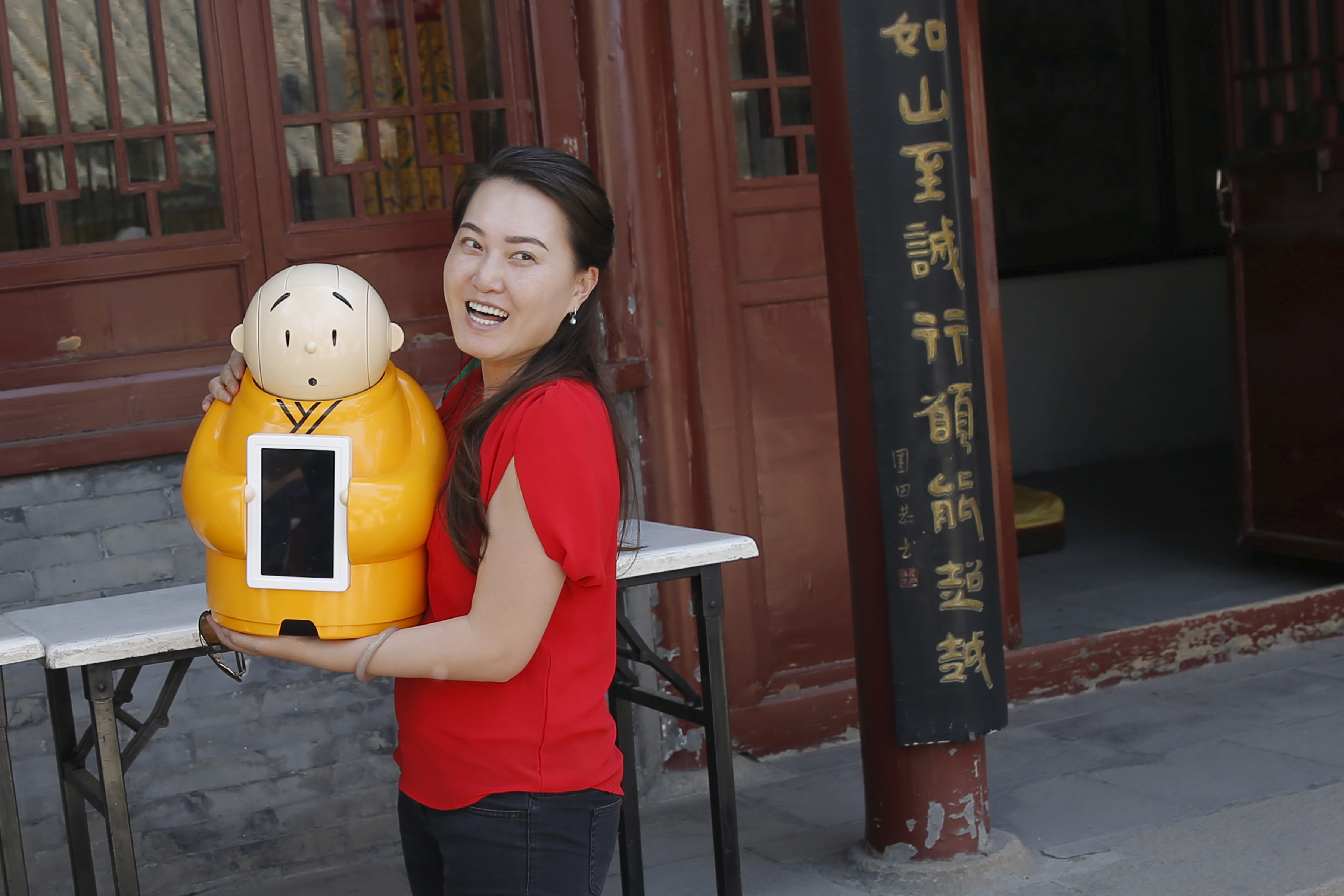 A visitor smiles as she holds Robot Xian'er which is placed in the main building of Longquan Buddhist temple for photograph by the temple's staff, on the outskirts of Beijing, April 20, 2016. REUTERS/Kim Kyung-Hoon