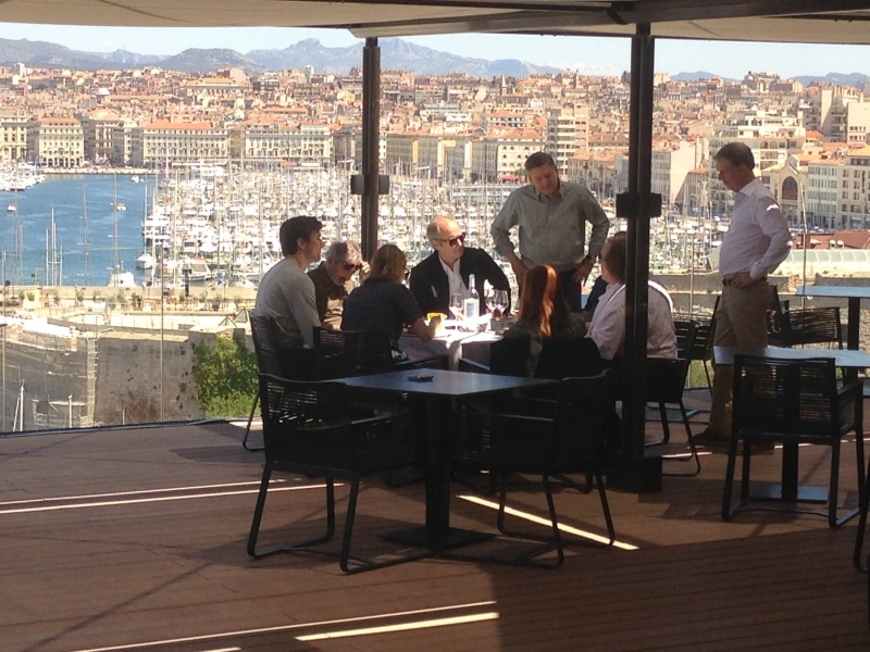 "Netflix's Ted Sarandos (standing, center) and Reed Hastings (standing, right), talk to the cast and producers of ""Marseille"" with the city's Old Port in the background."