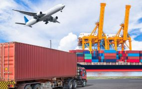 A truck pulls into a shipping port, with an airplane pictured overhead